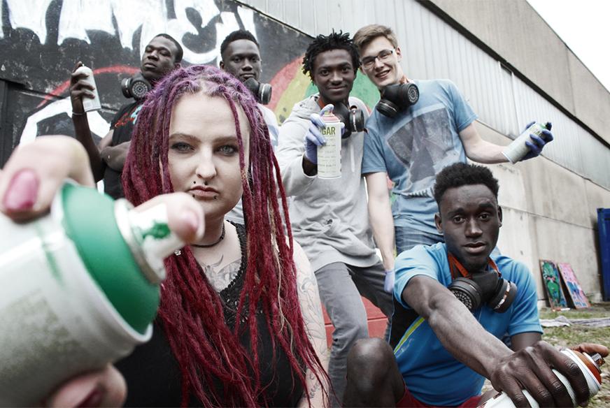 Gruppe junger Menschen vor einem Graffito