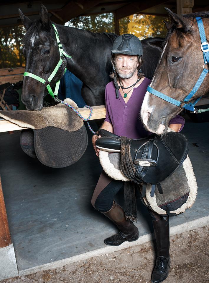 Informelles Portrait eines Reiters in einem Pferdestall.