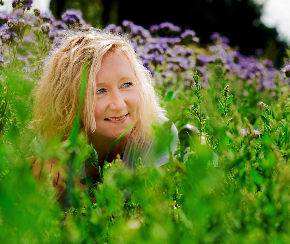 Junge Frau mit blonden Haaren liegt im grünen Gras.